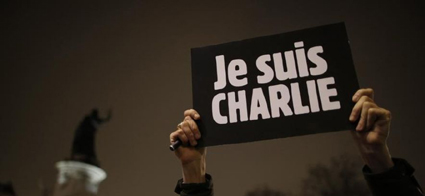 705601-a-man-holds-a-placard-which-reads-i-am-charlie-to-pay-tribute-during-a-gathering-at-the-place-de-la-